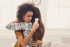 Femme étreignant son ami déprimé à la maison Images stock