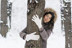 Femme étreignant un arbre dans la forêt d'hiver Nature affectueuse images libres de droits