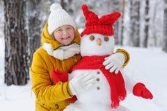 Femme étreignant un bonhomme de neige en parc d'hiver Image stock