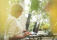 Femme aîné à l'aide d'un ordinateur portatif Photos stock
