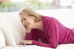 Femme aîné à l'aide de l'ordinateur portatif à la maison Image stock