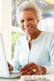 Femme aîné à l'aide de l'ordinateur portatif à la maison Photos stock