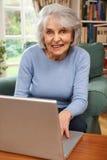 Femme aîné à l'aide de l'ordinateur portatif à la maison Images libres de droits