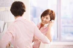Femme aîné à l'appel téléphonique, se reposant avec le collègue Image stock