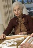Femme aîné à la table de jeu Photographie stock libre de droits