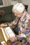 Femme aîné à la table de jeu Photographie stock