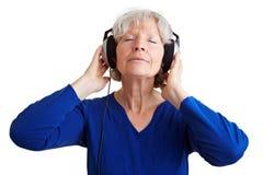 Femme aîné écoutant la musique Photographie stock libre de droits