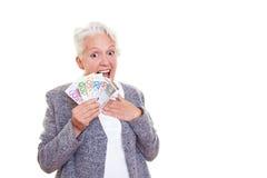 Femme aîné étonné avec de l'argent Photographie stock
