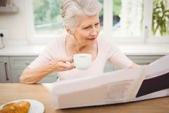 Femme aîné affichant un journal Images stock