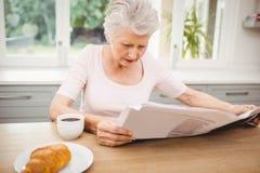 Femme aîné affichant un journal Photo stock