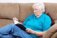 Femme aîné affichant un livre Images libres de droits