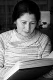 Femme aîné affichant un livre Photos stock