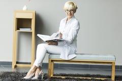 Femme aîné affichant un livre Image stock