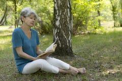 Femme aîné affichant un livre Photographie stock libre de droits