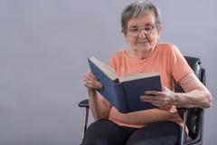 Femme aîné affichant un livre Photos libres de droits