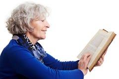 Femme aîné affichant un roman Images stock