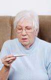 Femme aîné affichant un thermomètre Image libre de droits