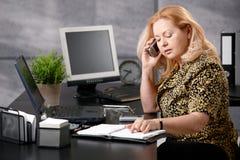 Femme aîné appelant dans le bureau Photo libre de droits