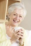Femme aîné appréciant la boisson chaude Photo stock
