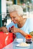 Femme aîné appréciant le casse-croûte au café extérieur Image libre de droits