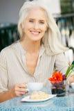 Femme aîné appréciant le casse-croûte au café extérieur Photo stock