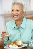 Femme aîné appréciant un repas à la maison Photographie stock libre de droits