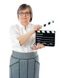 Femme aîné attirant utilisant le clapperboard Photos stock
