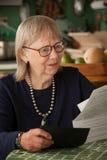 Femme aîné avec beaucoup de factures Image stock