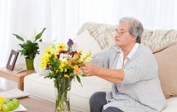 Femme aîné avec des fleurs Images stock