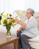 Femme aîné avec des fleurs Photo libre de droits