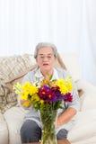 Femme aîné avec des fleurs Images libres de droits