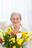 Femme aîné avec des fleurs Photo stock