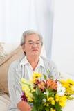 Femme aîné avec des fleurs Photographie stock
