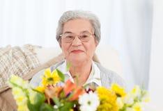Femme aîné avec des fleurs Photos stock