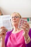Femme aîné avec des pillules et la prescription Photographie stock