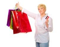 Femme aîné avec des sacs et par la carte de crédit heureux Image stock