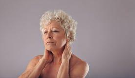 Femme aîné avec douleur cervicale Images stock