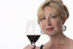 Femme aîné avec du charme retenant une glace de vin rouge Photo libre de droits