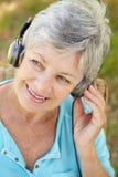 Femme aîné avec l'écouteur Photos stock