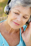 Femme aîné avec l'écouteur Photo libre de droits