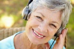 Femme aîné avec l'écouteur Images libres de droits