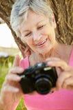 Femme aîné avec l'appareil-photo Photo stock