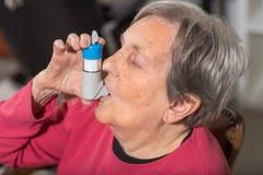 Femme aîné avec l'inhalateur d'asthme Images libres de droits