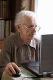 Femme aîné avec l'ordinateur portatif Images libres de droits