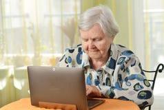 Femme aîné avec l'ordinateur portatif Image stock