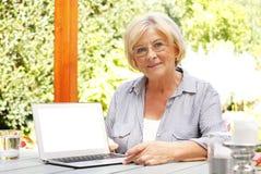 Femme aîné avec l'ordinateur portatif Image libre de droits