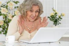 Femme aîné avec l'ordinateur portatif Images stock