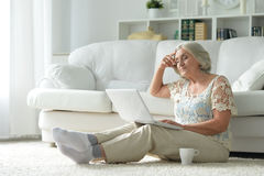 Femme aîné avec l'ordinateur portatif Photographie stock