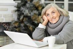 Femme aîné avec l'ordinateur portatif Photo libre de droits