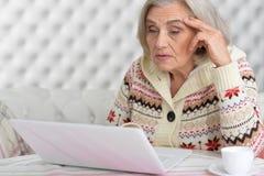 Femme aîné avec l'ordinateur portatif Photos stock